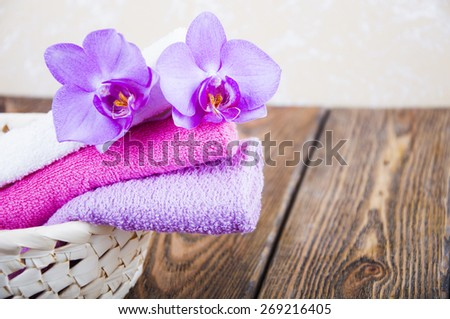 Bathroom soft and fresh towels folded in wicker basket with orchid on a wooden background - stock photo