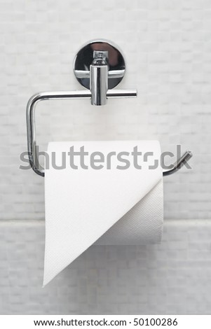 Bathroom tissue hanging on the wall. Toilet paper on white tiles - stock photo