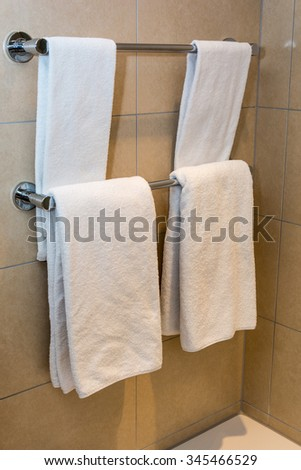 Bathroom Towels - white towels on a hanger prepared to use - stock photo