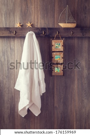 Bathroom wall with hanging towel and photo frame and toy boat - stock photo