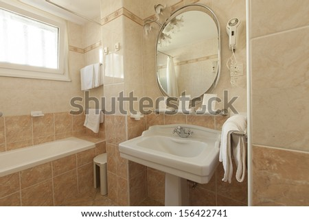 bathroom with beige tiles and decorations