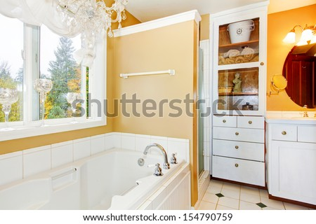 Bathroom with large white tub and storage cabinet. - stock photo