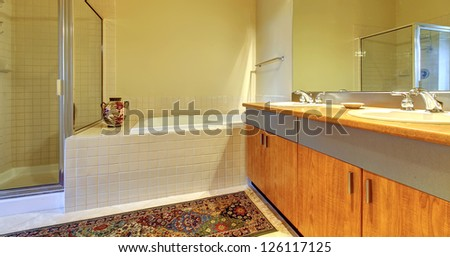 Bathroom with modern wood cabinets, tub and shower with yellow walls.