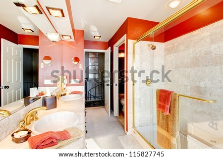 Bathroom with red walls and walk-in shower with beige tiles. - stock photo