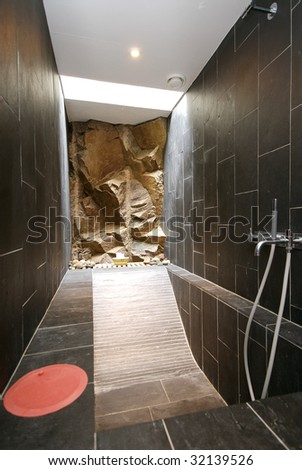 Bathroom with rocks coming in through the wall - stock photo