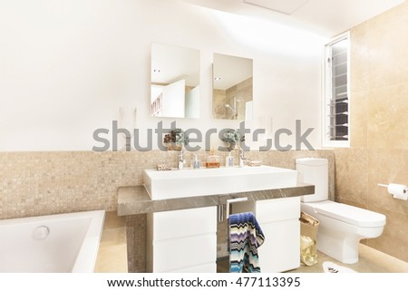 Bathroom with the toilet bowl and tap beside the sink and mirror with some fancy pants, the perfume and liquid glass bottles can be seen over the counter top