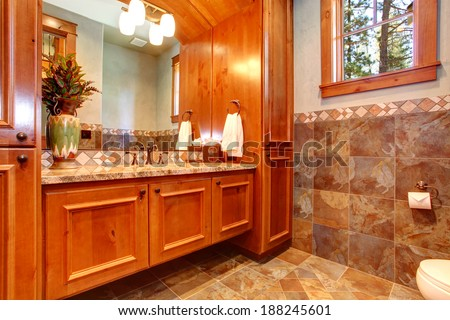 Bathroom with window and tile wall trim. View of furniture set with mirror and sink - stock photo