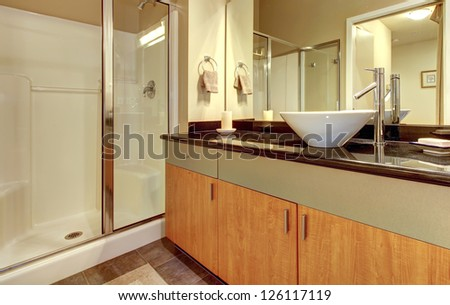 Bathroom with wood modern cabinets, glass shower and white sink. - stock photo