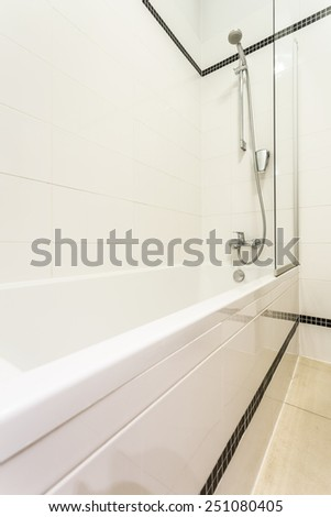 Bathtub in bathroom decorated with black and white tiles - stock photo