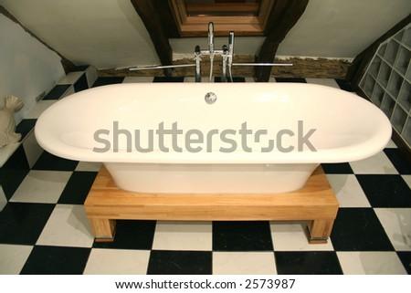 bathtub view on a black and white tile floor - stock photo