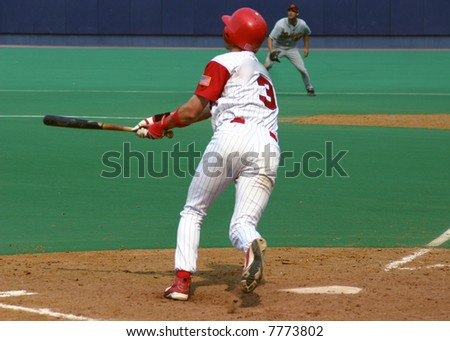 Batter watching his hit, baseball player on astroturf - stock photo