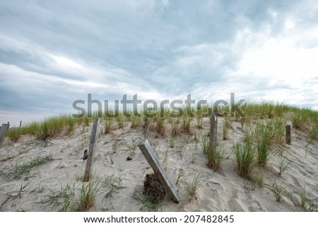 Battered East coast beach storm fence protecting tall sand dunes on a cloudy rainy day  - stock photo