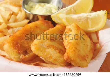 Battered fish sticks with french fries, lemon wedges and tarter sauce closeup