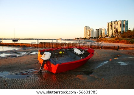 Battered old red dinghy with outboard motor lies on the beach at dawn. - stock photo
