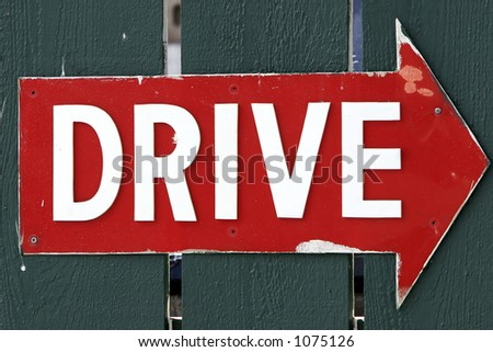 Battered Red Arrow Sign with the Word 'Drive' in White Letters. - stock photo