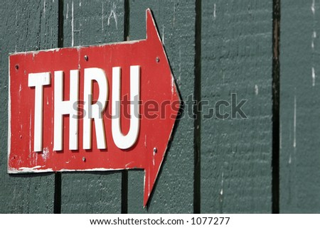 Battered Red Arrow with the word 'THRU' in White Letters (shallow focus). - stock photo