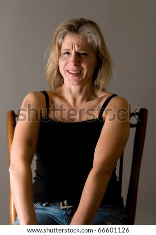 battered woman (bruises on face, throat, arm), breaks down - anger, rage, sadness - stock photo
