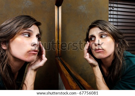 Battered woman checks the extent of her injuries in the bathroom mirror - stock photo