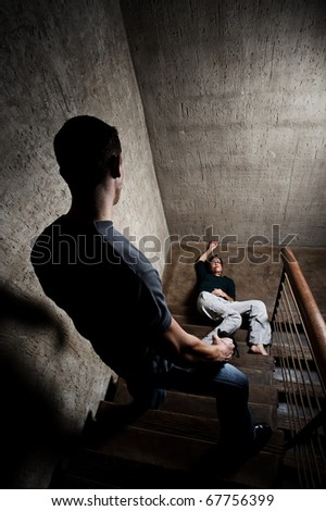 Battered woman lies lifelessly at the bottom of stairs, a conceptual shoot depicting the effects of domestic violence - stock photo