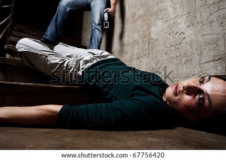 Battered woman lies lifelessly at the bottom of stairs with a faceless man holding a belt, a conceptual shoot portraying the process and effects of domestic violence - stock photo