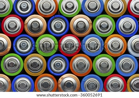 Batteries, top view, rows of alkaline battery AA size format in green, red, blue, bronze, gold, orange, colors, energy abstract background  - stock photo