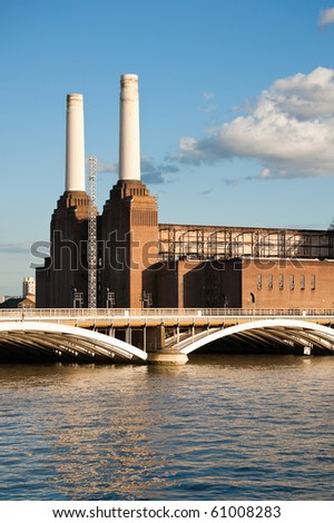 Battersea power station and bridge over the river Thames with reflection, against blue sky with white clouds - stock photo