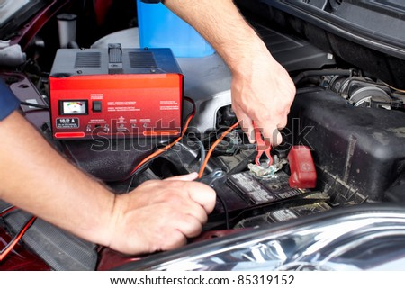 Battery charger and car in auto repair shop. - stock photo