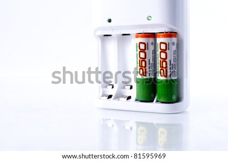 Battery charger on white background with two  AA batteries - stock photo