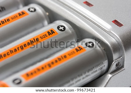 Battery charger with batteries AA background - stock photo