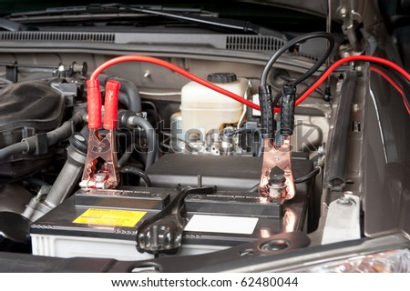 Battery charging cables transferring power to a dead battery. - stock photo