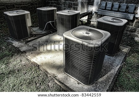 Battery of air conditioner condenser units outside an old building as part of a climate control cooling and refrigeration conditioning system - stock photo