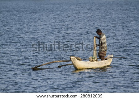 Batticalao, Sri Lanka - June 22, 2014: Traditional fisherman in dugout canoe in Sri Lanka. In Sri Lanka coast, poor people try to fish for they daily food - stock photo