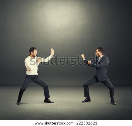 battle between two young businessmen in the dark studio - stock photo