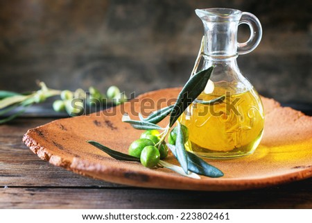Battle of olive oil with olive branch in handmade clay plate over wooden table. - stock photo