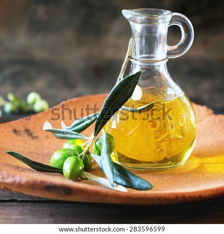 Battle of olive oil with olive branch in handmade clay plate over wooden table. Selective focus, square image - stock photo