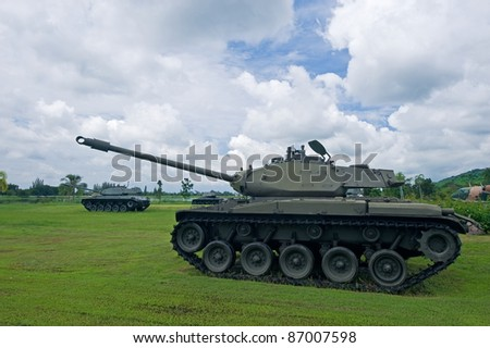 Battle tank with cloudy sky in background - stock photo