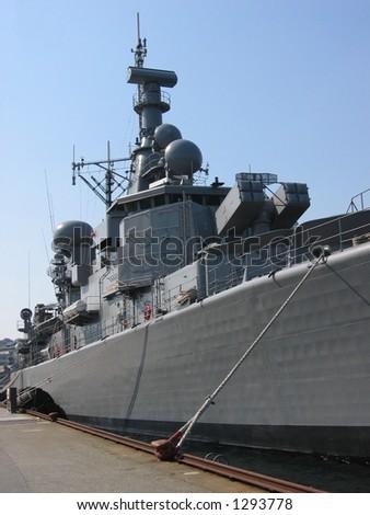 Battleship docked at a harbor - stock photo