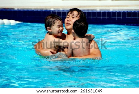 Batu Ferringhi, Malaysia - January 17, 2007:   Korean father holds his two young sons as they enjoy the swimming pool at a major resort hotel - stock photo