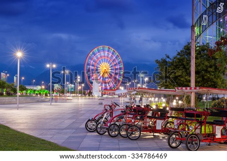 BATUMI, GEORGIA - September 18, 2015: Night view of Batumi - capital of Adjara, Georgia. Ferris wheel and bikes on seaside boulevard. - stock photo