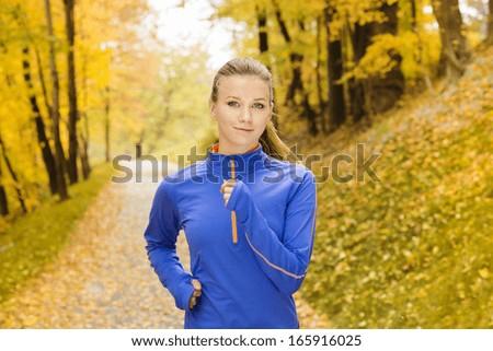 Bautiful running woman jogging in autumn nature - stock photo