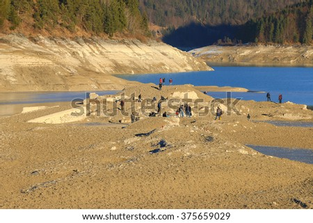 BAVARIA, GERMANY - DECEMBER, 2015 : People exploring the ruin of sunken old village Fall at Sylvenstein Reservoir dam in Bavaria, Germany on December 30, 2015. Village resurfaced during the renovation - stock photo