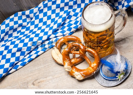 Bavarian beer mug and pretzels on a rustic wooden table - stock photo