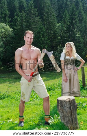 Bavarian couple in love in fashionable dress clothing for firewood work on a summer pasture in the mountains / Bavarian couple in love chopping wood in fashionable dress clothing - stock photo