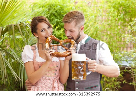 Bavarian couple in traditional costume with beer and brezel outdoor in a beergarden - stock photo