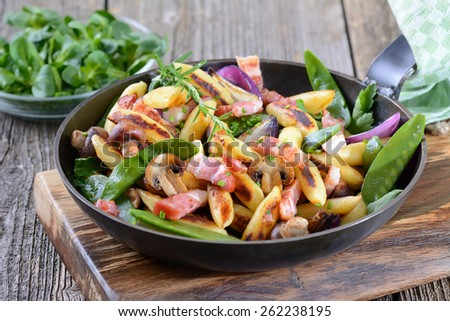 Bavarian fried finger-shaped potato dumplings with vegetable and smoked bacon - stock photo