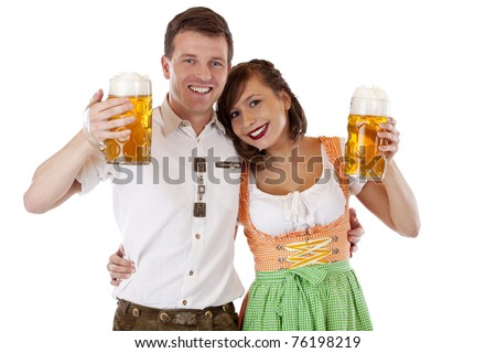 Bavarian man and woman in dirndl and lederhose with beer stein. Isolated on white background. - stock photo