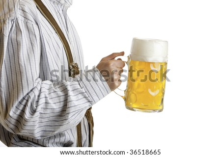 Bavarian man dressed in leather trousers (lederhose) is holding an Oktoberfest beer stein - stock photo