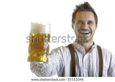 Bavarian man dressed with leather trousers is holding an Oktoberfest Beer Stein into camera. Isolated on white background.