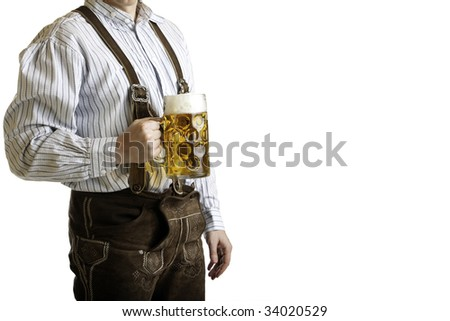 Bavarian man dressed with original leather trousers holds an Oktoberfest beer stein into the camera - stock photo