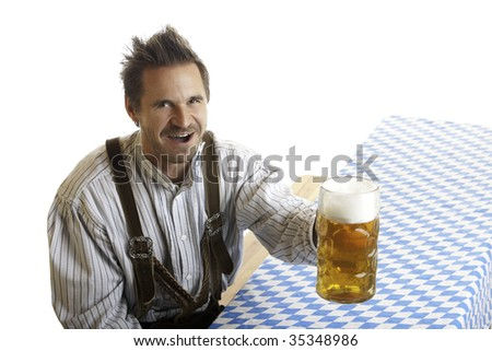 Bavarian Man dressed with traditional leather trousers (lederhosen) cheers with Oktoberfest Beer Stein in his hand. - stock photo